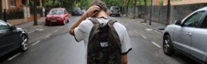 Teenage boy wearing backpack walks down the street